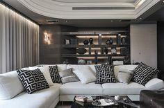 Tv-huone, tummat sävyt, sohva, tekstiilit, hyllyt, valaistus, materiaalit