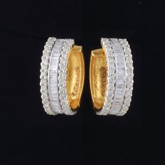 Stylish hoop earrings made of gold and has been studded with round cut diamonds and baguette cut diamonds. The front is diamond studded while the back is of plain gold without any design.