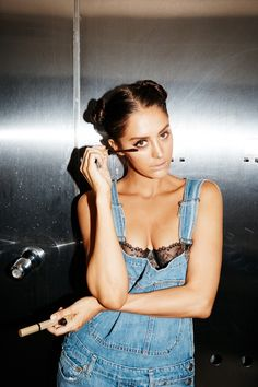 How Moxie Raia Got Ready for Our 5 Year Anniversary Party: Wearing a Black Lace Bralette under Light Wash Denim Overalls with Double Buns while doing mascara | coveteur.com