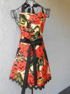 Jack O Laterns with black cats reverses to polka dots, has a fuller skirt, 4 pockets and long ties that can wrap around