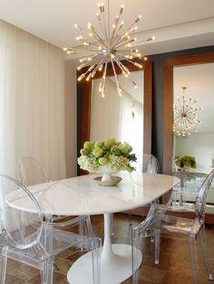 Sala de jantar clean. Mesa tulipa, cadeiras em acrílico e luminária sputnik