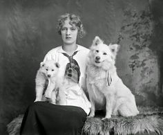 Studio portrait of a young woman with two husky dogs, ca. 1920s
