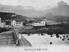 Se ve en esta imagen del muelle oeste del Puerto de la Cruz el desaparecido Charco de Cha Paula a mar vacía y, a la izquierda, la inconfundible imagen de la Casa Yeoward y la Casa Franchy, hoy desgraciadamente desparecidas. Aunque muy difuminado, también se aprecia el edificio de la antigua pescadería y allá en lo alto, casi cubierto de nubes, el Pico Teide. Tenerife, Train, Outdoor, Boat Dock, Volcanoes, Antique Photos, Clouds, Past, Teneriffe