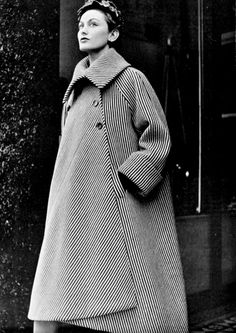 Model in ample coat of a soft woolen black and white stripe with deep cuffs and fold-over collar by Balenciaga, photo by Pottier, 1950