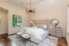 Restful bedroom boasts a light beige velvet tufted wingback bed dressed in white and gray bedding accented with a light gray throw and gray sheepskin pillows.