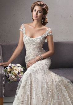 Exquisite beaded embroidered lace on tulle drapes over delustered satin in this fit and flare gown featuring dazzling Swarovski crystals on the neckline and shoulder straps. Complete with scoop neckline and finished with crystal button and zipper over inner corset closure. Optional detachable, cold shoulder cap-sleeves.
