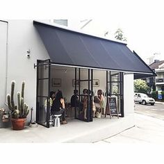 Cute cafe interior, floor to ceiling windows that open up with a simple awning, black and white design and a cactus plant out front