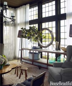 Tall windows with sweeping views of Lake Martin dominate the living room. An antique Belgian wheel is displayed on a console from Bobo Intriguing Objects. A pair of antique stools next to Garden Park Antiques' Reclaimed Oak Trefoil table accommodate the owners' six-year-old twins. Sunlight filters through curtains in Rose Brand's Cotton Scrim. Workshop floor lamp from Blue Ocean Traders. Oushak rug, Designer Carpets.   - HouseBeautiful.com