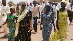 Rour female students of the government secondary school Chibok, who were abducted by gunmen and reunited with their families, walk in Chibok, Nigeria (21 April 2014)
