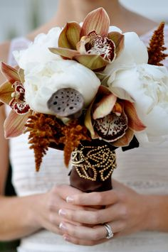 White peonies with burnt orange cymbidium orchids, dried lotus pods, and rust colored filler -- all wrapped with chocolate brown satin and edged with gold beaded leaf embroidery. Such an elegant autumn / fall bouquet!