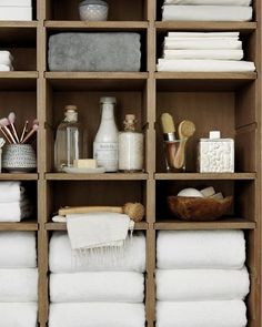 Ballard Designs oak Beckett cabinet used in a master bathroom with fluffy towels, bed linens, and toiletries