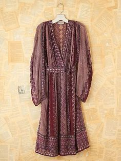 """Vintage floral and dot patterned mid-length dress with deep """"V""""-neckline and elastic waist. Pleating in fabric at top of each shoulder. Long, slightly oversized peasant sleeves. Comes with matching patterned waist tie belt."""