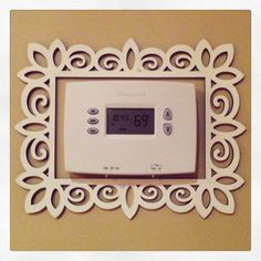 Cute inexpensive way to dress up a plain thermostat. Wood frame from Michaels (only $2.99) painted in your choice of colors!