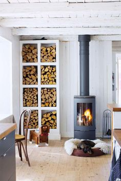 Modern And Cool Home Wood Burning Stove A Scandinavian space with a modern and cool wood burning stove plus an elegant open storage unit for firewood. Wood Stove Decor, Cabin Design, House Design, Freestanding Fireplace, Cabin Homes, Firewood, Living Room Designs, House Plans, New Homes