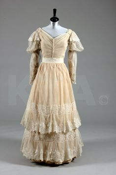 A needlerun lace bridal/summer gown, circa 1830, with floral embroidered, tiered tulle skirt, V-pleats to front bodice, and puff sleeves with satin piping
