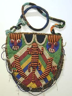Yoruba Bag   NIgera   Used to carry divination objects and tools, the bags are worn in public ceremonies by Ifa priestesses and used and displayed in their homes. Beads were signs of wealth and status. The beaded front lifts up to reveal a pouch on the back panel.