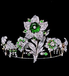 Chaumet - An antique Transformable tiara with lily motif, circa 1830. Belonged to the Leuchtenberg family, descendants of Empress Joséphine. The large hexagonal emerald solitaire can be worn as a brooch.