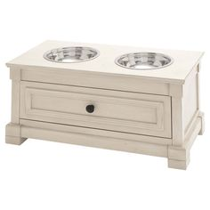 """Bring a classic touch to meal time with this wood pet diner, featuring a paneled design and 2 steel bowls. Construction Material: Wood and steel Color: Cream Features:  Bowls included; Spacious drawer Dimensions: 12"""" H x 24"""" W x 12"""" D"""