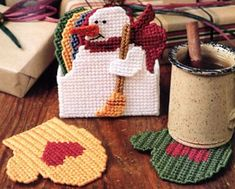 "Snowy Day Coaster Set Plastic Canvas ePattern - This broom-toting snowman is ready to warm up chilly winter days for your favorite folks. Our adorable friend makes a cute holder for handy mitten coasters that are stitched to look like they're really knitted!Designs are worked on two 101/2"" x 131/2"" sheets of clear 7 mesh plastic canvas using worsted weight yarn and embroidery floss. Cork or felt may be glued to back of coasters. Number of Designs: Snowman box and 6 mitten coasters…"
