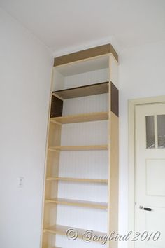 Take a billy bookcase from IKEA, add 2 extensions and crown molding on top, beadboard wallpaper in the back, and a coat of primer/paint...you have a DIY BUILT-IN BOOKCASE!
