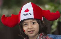 A young boy smiles as he watches the annual Canada Day parade in Montreal, Monday, July 1, 2013. - THE CANADIAN PRESS/Graham Hughes