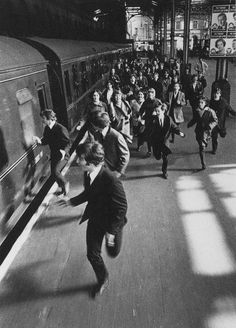 Beatles running for the train from amorous fans.