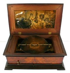 """Symphonion Symphonium Music Box, serial number 108949.  Includes ten 11.5\"""" discs.  In exotic hardwood veneer case, fits on stand with drawer for storing discs.  Music box; 8 1/2\"""" H x 24 1/2\"""" W, stand; 5 1/2\"""" H x 17 1/2\"""" D.  Lithograph under lid with water damage, creases, tears, and loss.  Very good working condition.  Appears all original."""