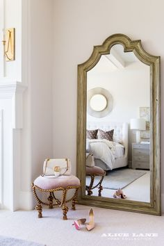 Floor length mirror and velvet ottoman inside blogger, Emily Jackson's, master bedroom. Perfect spot to slip on shoes. (both mirror and ottoman are 20% off now through september 30th on www.alicelanehome.com) Designed by Alice Lane Photo by Lindsay Salazar