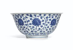 A LARGE BLUE AND WHITE 'LOTUS' BOWL MARK AND PERIOD OF JIAJING the deep rounded sides rising from a slightly tapered foot to a flared rim, the exterior decorated in various tones of cobalt-blue with a continuous band of lotus blossoms borne on an undulating scroll issuing stylised curling leaves, all above a band of upright stylised ruyi-shaped lappets bordering the bowl, the interior centred with a medallion enclosing four lotus blossoms wreathed in trefoil leaves stemming from a thin stem
