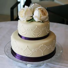 Wedding Cake - 2 tier, purple with silk ribbon and hand embellished pearl piping.