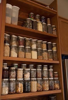 Organize with canning  jars....I don't have nearly this much dry goods to store, but they are WONDERFUL for fridge/left-overs storage.....you can see what's in there....and the smell doesn't get out ....as w/onions!