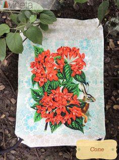 Cone: Representación de los colores de la primavera y los días de pascua con jardines frondosos, inundados por una exuberante paleta de colores vivientes en forma de flor. El rojo energiza el diseño convirtiendo el bolso en un accesorio lleno de dinamismo natural que llama la atención a donde vas. Es la emoción pura de la naturaleza transformada en la mejor postal ambulante que puedes sacar a pasear.  Costo 40,000$ Medidas 29X43 Algodón 100%