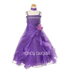 Midnight Wave Sparkling Purple Flower Girl Dress: This gorgeous purple dress features thin double straps with sprinkles of rhinestones crystal cascading down to accentuate the bodice. The natural waist is accented with a gorgeous detachable satin flower corsage. The tea length skirt is made with a sheer, crystal organza; a soft and gentle fabric that just flows! The light skirt is enhanced with multiple ruffles of sheer organza with an overlay wrap-around layer that adds a daring flare!