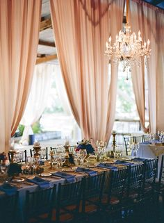 glam barn wedding- complete with lofty ceiling, pale coral draping, and crystal chandeliers
