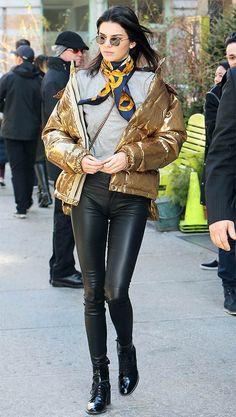 Street style look Kendall Jenner com calça de couro, t-shirt, puffy jacket e bota de verniz.
