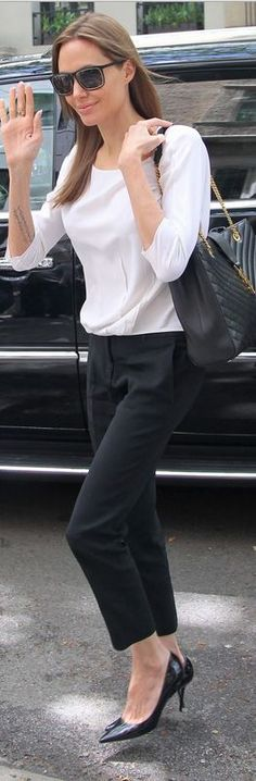 Angelina Jolie: Sunglasses and purse – Saint Laurent  Pants and shirt – Michael Kors  Shoes – Jimmy Choo