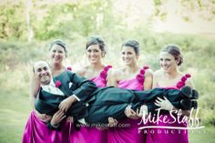 bridesmaids holding up the groom