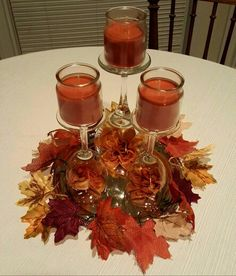 DIY fall centerpiece. Quick, easy, and under $10 from Dollar Tree! Includes: 1 nickel plated tray, 1 burlap maple leaves arrangement, 1 orange floral arrangement, 1 large wine glass, 2 small wine glasses, and 3 small jar pumpkin scented candles