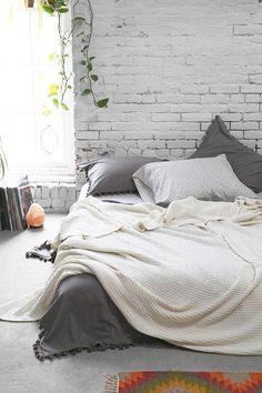 Grey and white bedroom with exposed white brick wall