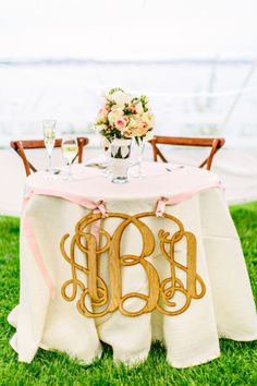 Sweetheart table with monogram decor: http://www.stylemepretty.com/massachusetts-weddings/cape-cod/2015/06/29/romantic-cape-cod-wedding-at-winslow-estate/ | Photography: Kelly Dillon - http://kellydillonphoto.com/