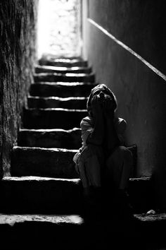 Black and white photography | Photo in low lighting of a child sitting on the stairs deep in thought