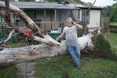 Allen Cook talks on his cellphone as he stands next to a downed tree in a mobile home park west of Shawnee, Okla., where several homes were destroyed by a tornado.