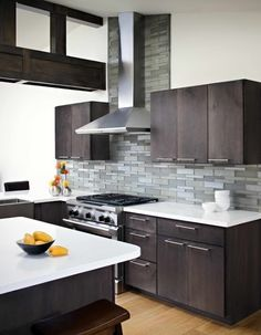 A textured backsplash & wall accent of various shades of grey gives this island kitchen layout a nice splash of modern design to match the modern walnut cabinets.