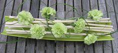 Boeket anjers als bloemstuk verwerken in een horizontale constructie van takken boeketten