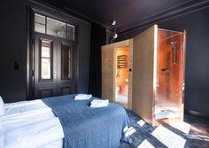 Navy hotel room with brass freestanding bathroom