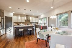 contemporary kitchen idea with eating area white corner cabinets white top kitchen island with dark toned wood base medium toned wood floors white dining chairs with wood base round glass dining table of Corner Cabinets for Dining Room: Adorable and Functional Storage Option for Eating Area