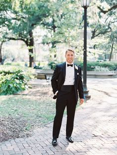Groom looking dapper in a classy black tux: http://www.stylemepretty.com/georgia-weddings/savannah/2016/09/12/a-traditional-southern-cathedral-wedding-bathed-in-blue/ Photography: The Happy Bloom - http://www.thehappybloom.com/