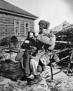 Soviet soldier taking care of a war orphan, Russia, 1943; note PPSh-41 submachine gun in soldier's lap