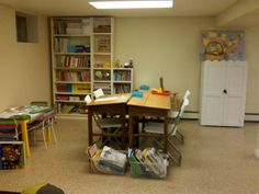 """Our classroom is in a section of our basement playroom.  We've set aside an area for desks, a small table for art, a book center, and a multifunction storage cabinet that doubles as a showcase for artwork when it's opened up.  The desks are former architect tables that we picked up at an antique warehouse while on vacation one year!  We paired them with really inexpensive chairs from our favorite Swedish store {where we got the bookcases and art table as well}."""