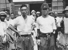 Japanese army interpreter (right) and a Korean policeman with a group of Korean…